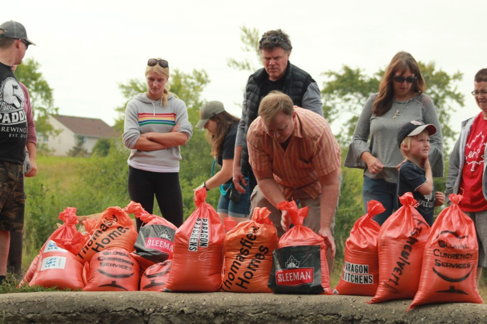 Program manager of trails and natural area stewardship Dave Beaton moves sandbags. Anam Khan/GuelphToday
