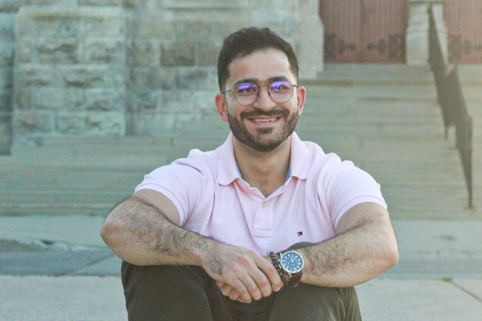 Tamim Holoubi sits in front of the Basilica of Our Lady Immaculate in Guelph. Anam Khan/Guelph