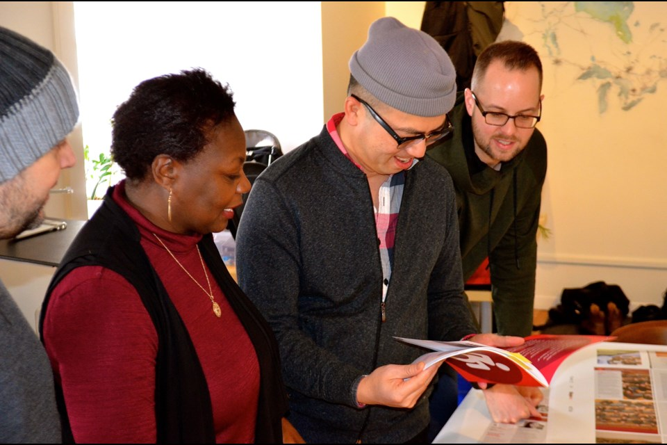 Festival director Marva Wisdom, accessibility and culture of care lead Coman Poon, and executive director Shawn Van Sluys proof the Accessibility Guide at their office on Dublin Street. Troy Bridgeman/GuelphToday