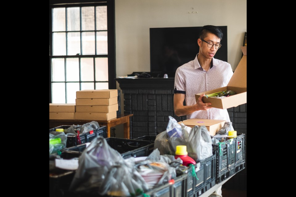 The Community Company founder Justin Chan prepares Wellness Boxes for low-income families. Supplied photo