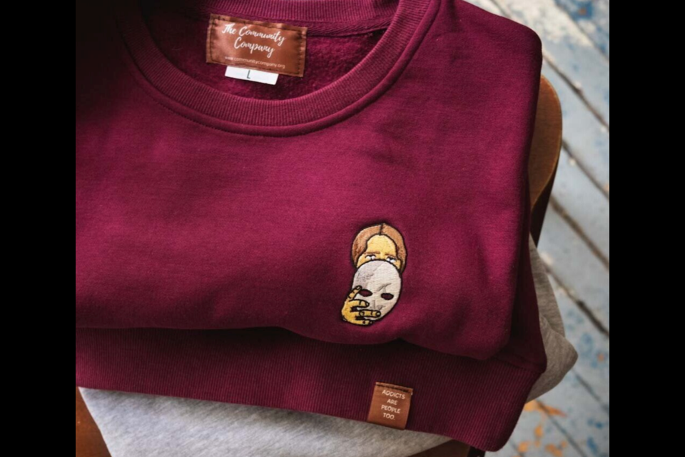 The sweater shows an image of a boy holding a mask towards his face.