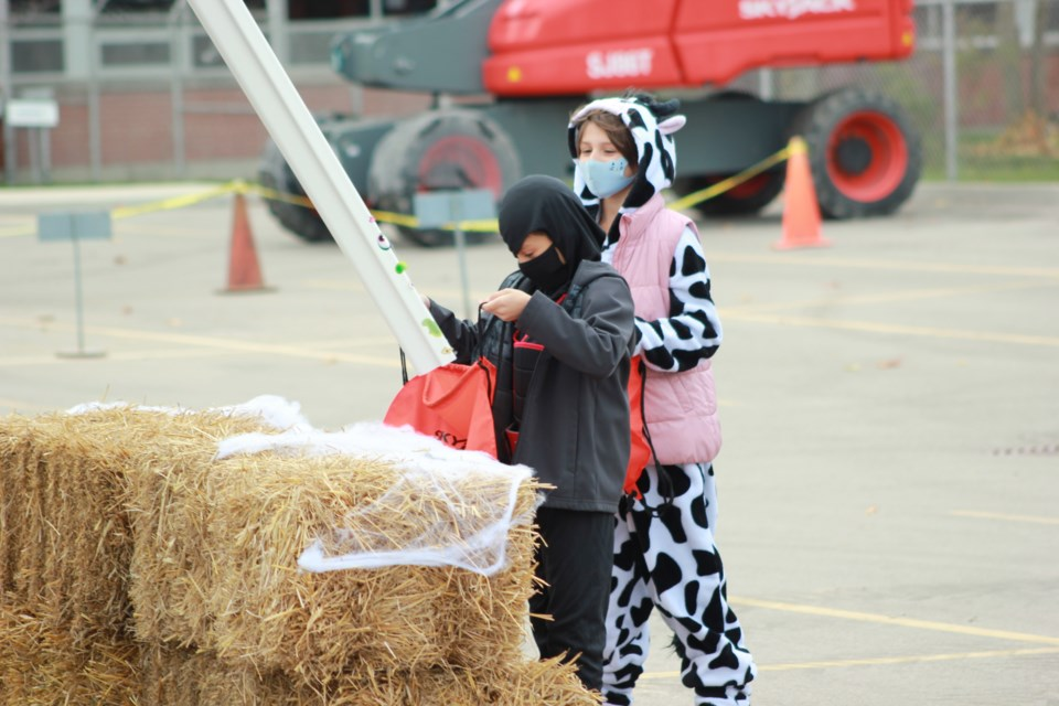 Children collect their candy through chutes coming from ccess equipment machines. Anam Khan/GuelphToday