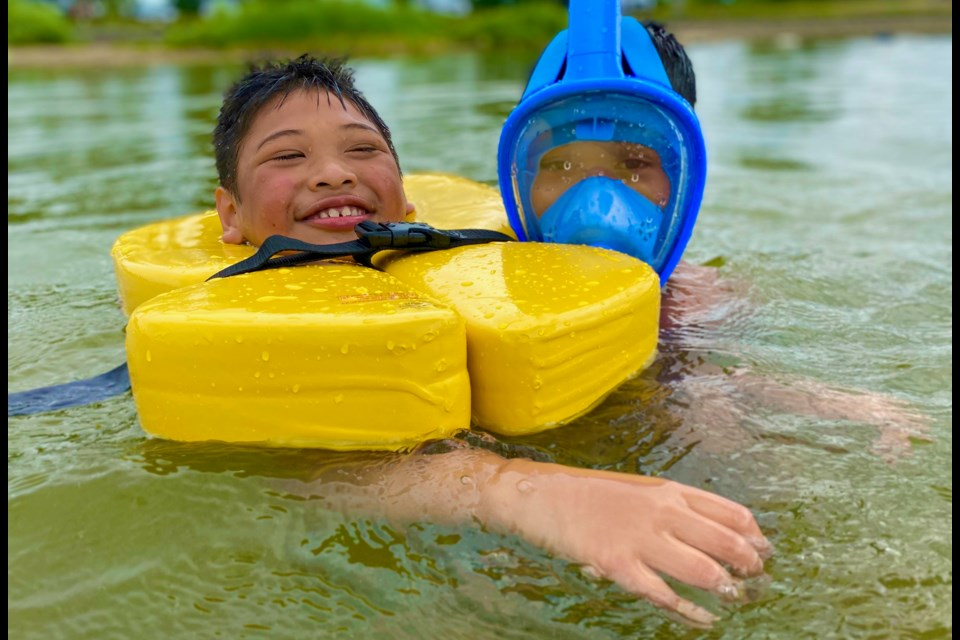A Wish Fund child swims with his brother during a family vacation.