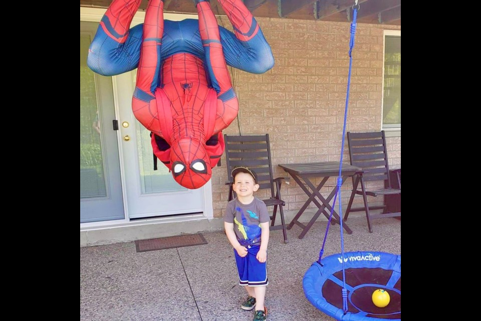 Spiderman hangs upside down on the deck to cheer a child up. Supplied photo