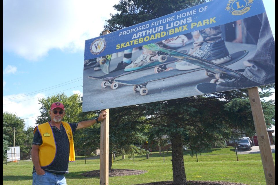 Lions club member Al Rawlins poses with a sign at the future site of the Brent Barnes Memorial Skatepark.