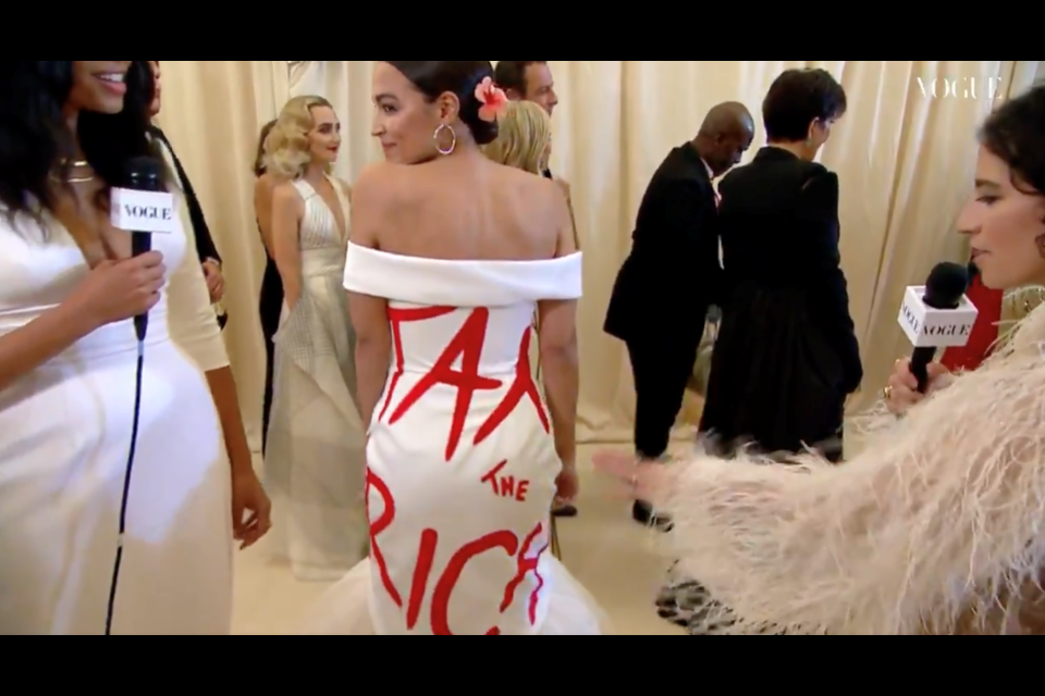 A screenshot of a video from Vogue's Met Gala that shows Alexandria Ocasio-Cortez's dress from the back with a message that reads 'TAX THE RICH.'