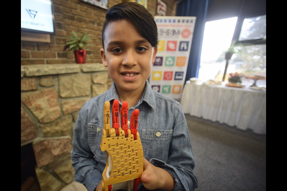Jordan Singh, 7, holds the prosthetic hand Thursday, March 1, 2018, made for him by a 3D printer at College Heights Secondary School. Tony Saxon/GuelphToday