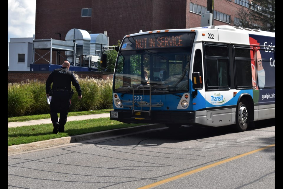 A Guelph police officer investigates the scene of a collision between a pedestrian and a Guelph Transit bus on Delhi Street.
