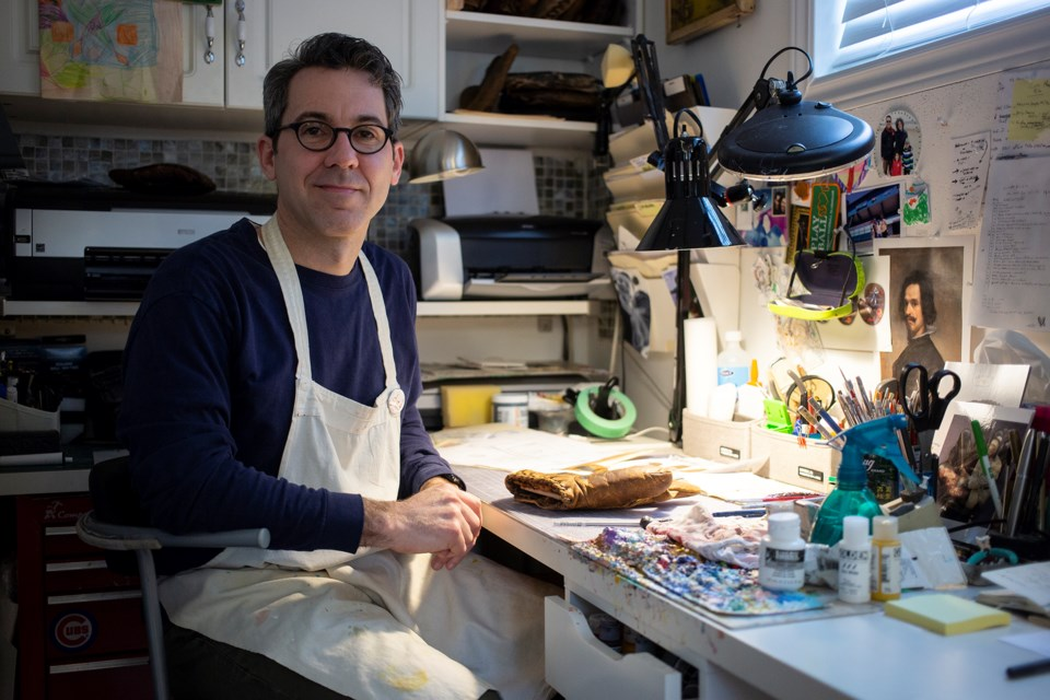 Sean Kane seen in his home studio in Guelph. Kane has found an interesting niche market by creating commemorative painted baseball gloves. Kenneth Armstrong/GuelphToday