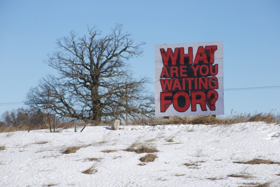 A hand-painted sign with the words 'what are you waiting for?' has popped up on the former Lafarge lands, future site of The Silvercreek Junction development. A different sign with the same wording appeared at the same site prior to 2014. Kenneth Armstrong/GuelphToday