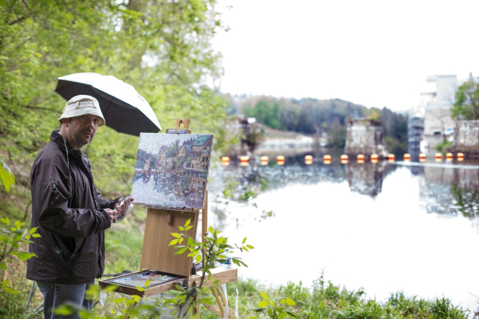 Michael Brennan paints a scene on Elora's waterfront for one of his possible entries in the Elora en Plein Air painting festival. Kenneth Armstrong/GuelphToday