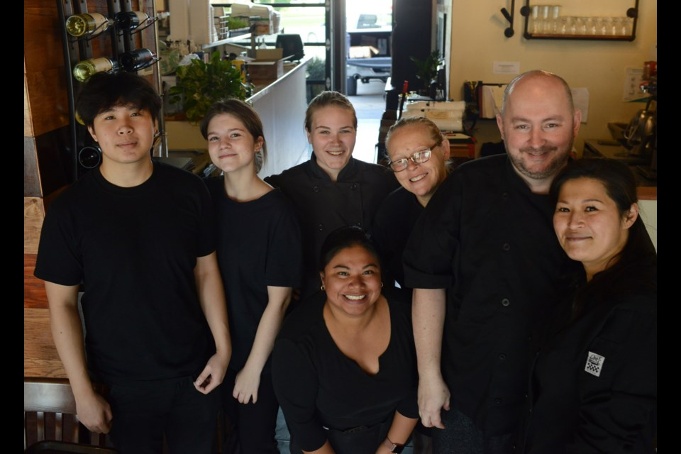 Staff and volunteers at Queen's Café, including owners Ron Hill and Tammy Hsieh, right, pose for a photo in the restaurant on Monday as hey prepare to serve 100 free Thanksgiving dinners as a way of giving back to the community. Tony Saxon/GuelphToday