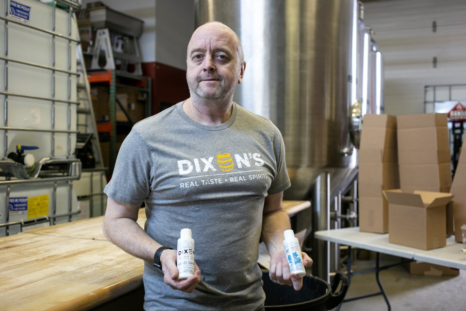 Volunteer Larry Gable holds up bottles of hand sanitizer produced at Dixon's Distilled Spirits in Guelph. The hand sanitizer is being distributed for free to local health care providers and frontline workers. Kenneth Armstrong/GuelphToday