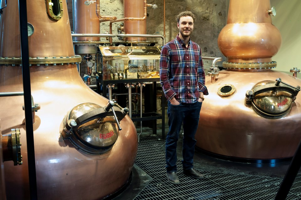 Cooper Sleeman stands next to the hand-made stills used by Spring Mill Distillery. The stills were built in Scotland and transported to the distillery by ship. Kenneth Armstrong/GuelphToday