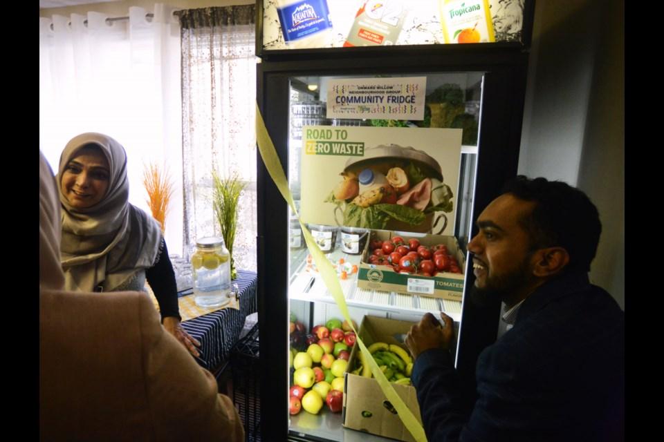 Road To Zero Waste creators Laylo Atakhodjaeva and her husband Shabeeb Hasan fill the new community food fridge at Onward Willow Community Centre Saturday. Tony Saxon/GuelphToday