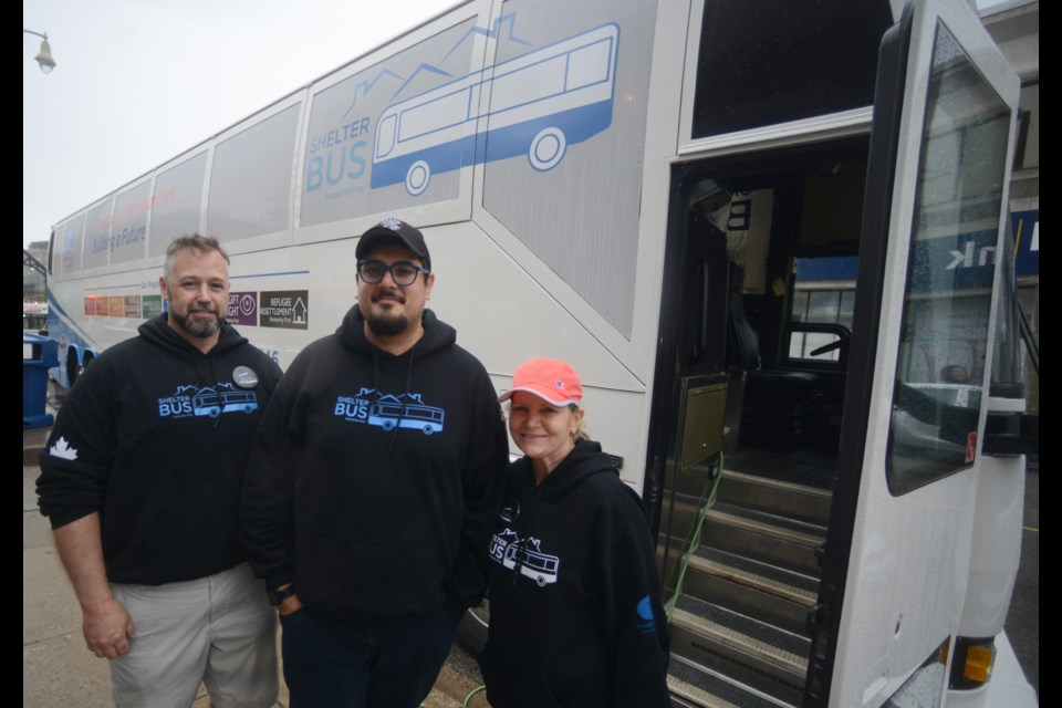 Denny Culbert, Naeem Farooqui and Sharon Nezny stand outside the Shelter Bus during its stop in Downtown Guelph on Saturday. Tony Saxon/GuelphToday