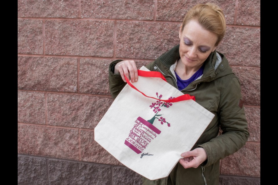 Jillian, a Community Company partner from Newfoundland, poses with a tote bag she created the design for. Supplied photo