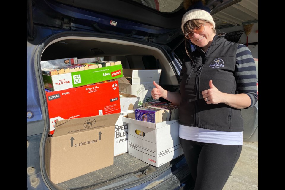 Helen Vanos poses with donated books and puzzles that will be sent to seniors homes in Guelph. Supplied photo