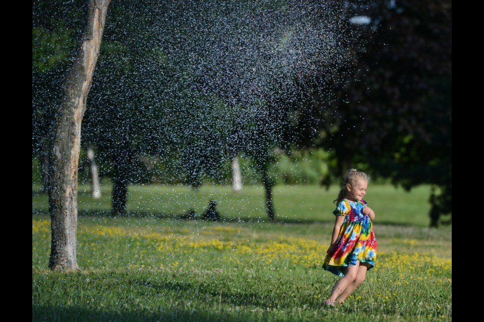 A young girl escapes a blast of water as the Guelph Fire Department's Hot Summer Night event kicked off Thursday at Margaret Greene Park on Westwood Road. Tony Saxon/GuelphToday