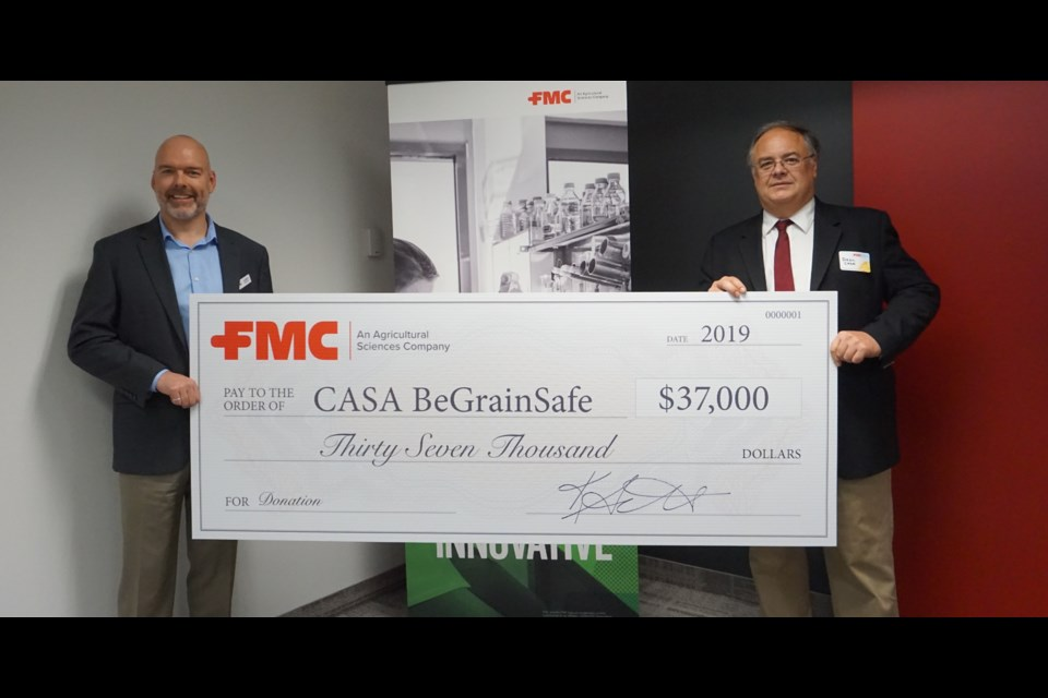 Guelph's Dean Anderson (right) accepts this donation from FMC Canada Country Manager Darren Dillenbeck in support of the BeGrainSafe program. Photo by Joey Sabljic