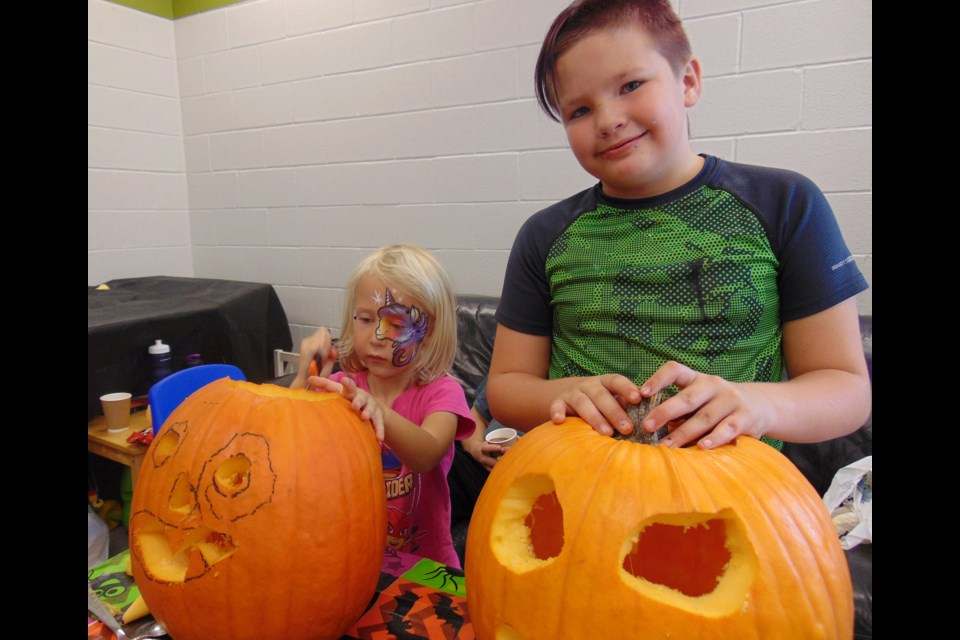 Nevaeh Payne and Owen Edwards get to work at the Grange Hill East Neighbourhood Group Family Pumpkin Carving at Ken Danby Public School Sunday. Barbara Geernaert for GuelphToday