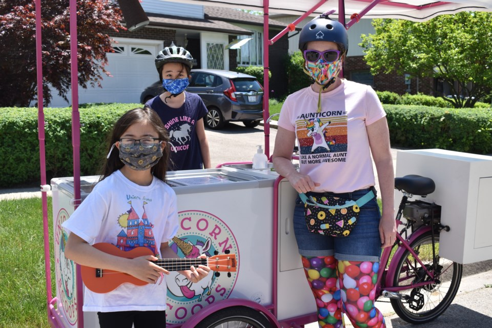 Amelia Ting, left, and Charlotte Ting, centre, wrote their own Peppa Pig-inspired jingle for Leah Nielsen's unicorn-themed ice cream business. Taylor Pipe photo