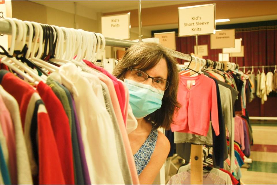 The Clothing Closet coordinator Lisa Burke peeks through a clothing rack.
