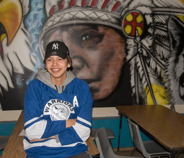 Kashechewan student Wade Hookimaw sits in front of mural in Doug Edwards' classroom. Philip Maher for GuelphToday.com