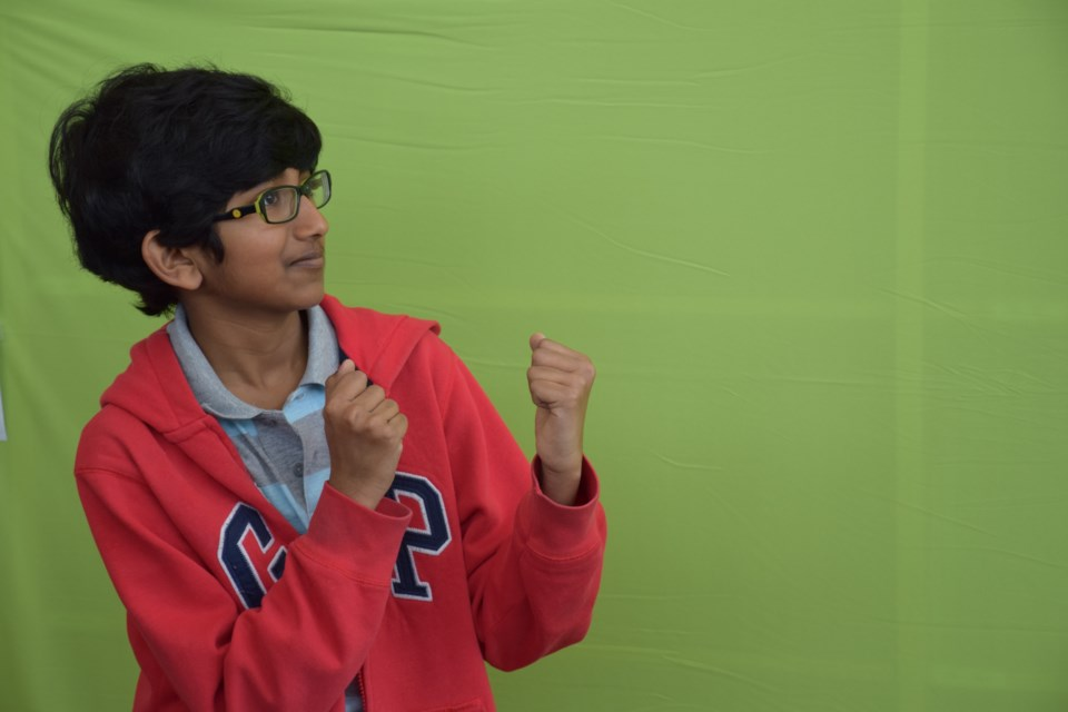 Rohan Patankar, 11, puts his dukes up in front of a green screen. A few steps on a computer screen showed him going up against Darth Vader.