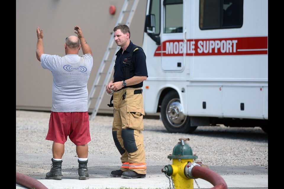A representative of Superior Spray Foam talks to a firefighter at the scene of a fire Monday, Sept. 5, 2016 on Elizabeth Street. Tony Saxon/GuelphToday
