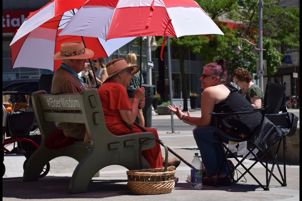 Norm Jary and Lola Jobst sit on the Schlegel Villages Green Bench in St. George's Square on Tuesday, sharing wisdom with Tammy Desjardins.