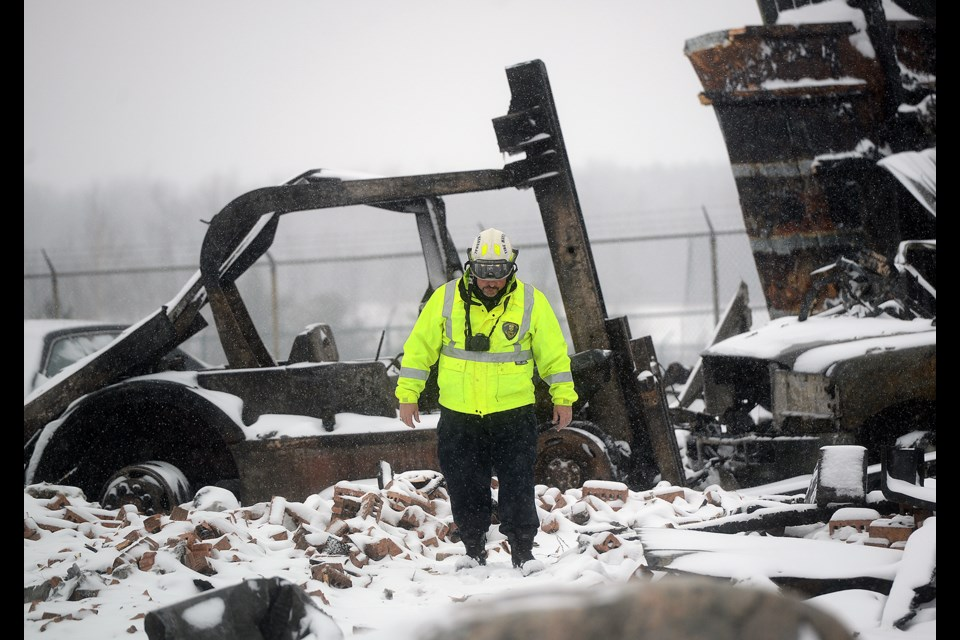 Ontario Fire Marshall's Office investigator Manny Garcia looks through the remains of a fire Tuesday morning that destroyed two buildings and a number of vehicles Monday, Jan. 9, 2017, on Highway 7 just west of Rockwood. Tony Saxon/GuelphToday