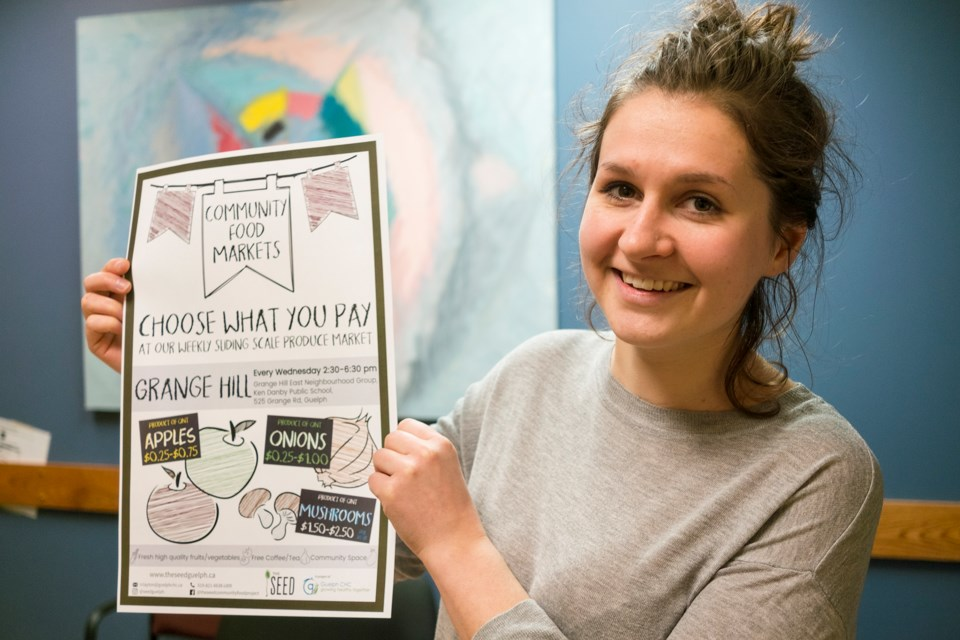 Rebecca Clayton, organizer of the Community Food Markets, poses with a flyer for the program's expansion into Guelph's east end, which starts next week. Kenneth Armstrong/GuelphToday