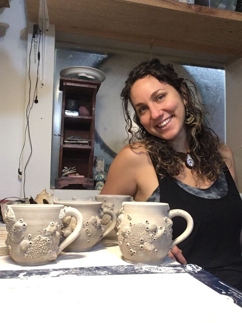 1. Annie Burgess with her barnacle mugs ready to be bisqued. Image provided by the artist