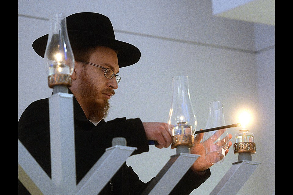 Shraga White lights the menorah in memory of his father Jeff, a pillar of the local Jewish community who passed away earlier this year. Tony Saxon/GuelphToday