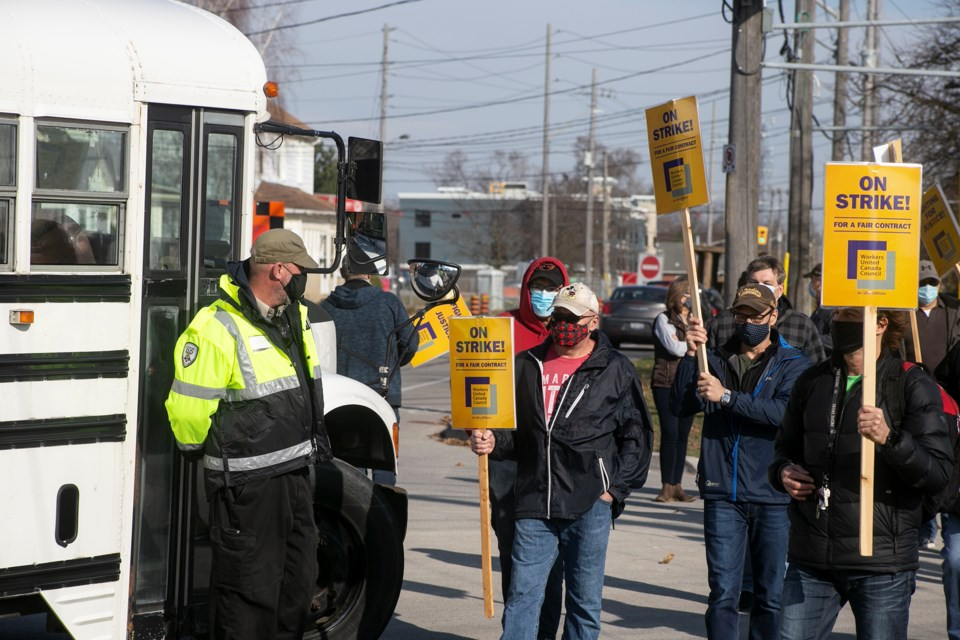 A security guard stands at the front door of a bus attempting to cross the picket line at Owens Corning on Friday. Kenneth Armstrong/GuelphToday