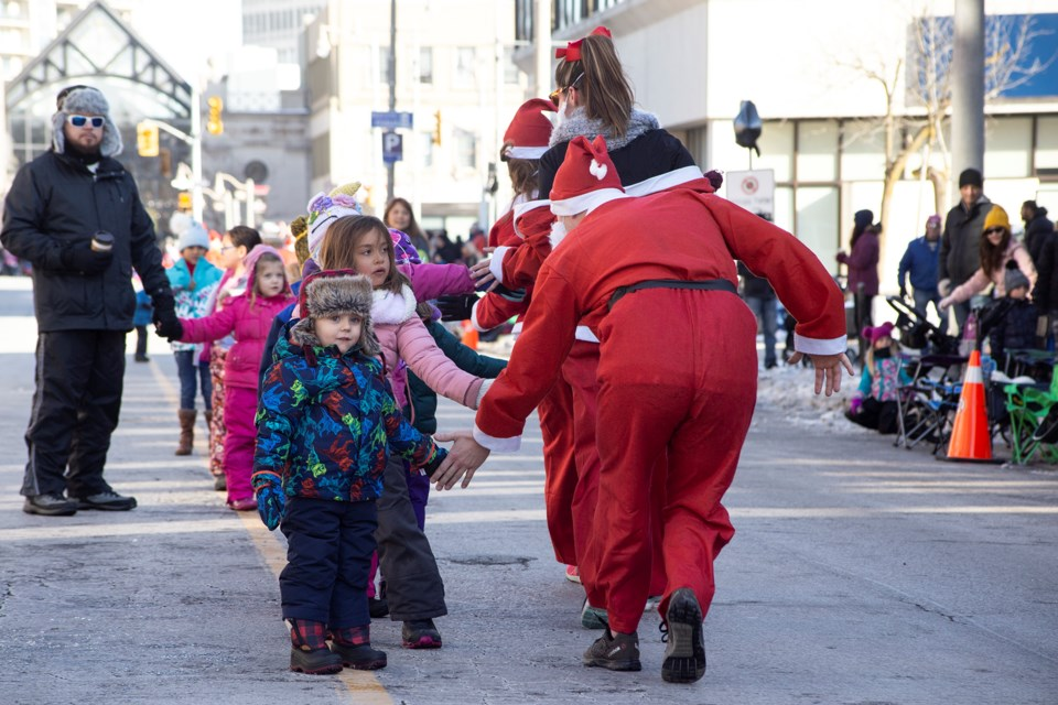 Participants in the Guelph Santa Parade Run get high fives from kids along the route on Sunday. Proceeds from the pre-parade event go to support Big Brothers Big Sisters of Guelph. Kenneth Armstrong/GuelphToday