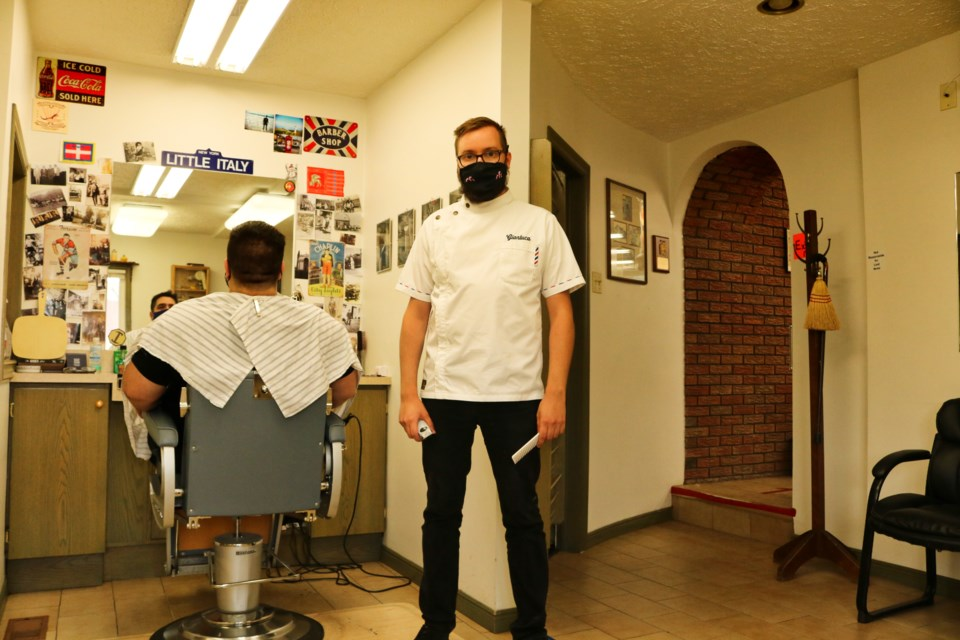 Barber and owner of Freddy's Barber Shop, Gianluca Prigione, stands at his chair in the second room of Freddy's. Ariel Deutschmann/GuelphToday