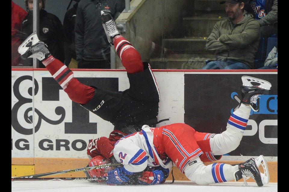 The Guelph Storm's Isaac Ratcliffe topples over Kitchener's Kole Sherwood Sunday, April 1, 2018, at the Sleeman Centre. Tony Saxon/GuelphToday