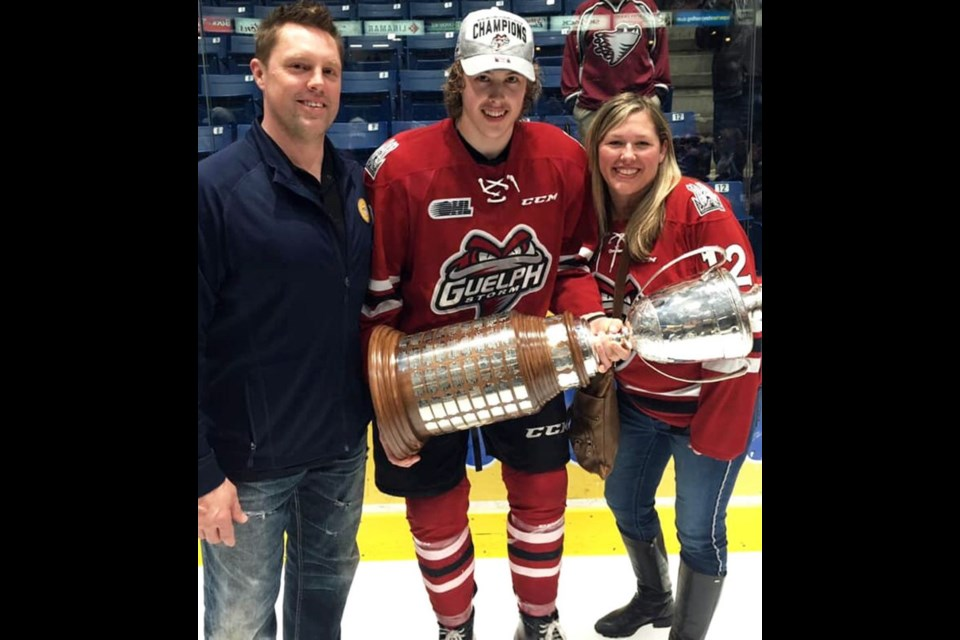 Keegan Stevenson poses with the OHL championship trophy with dad Jeremy and mom Selena. Family photo