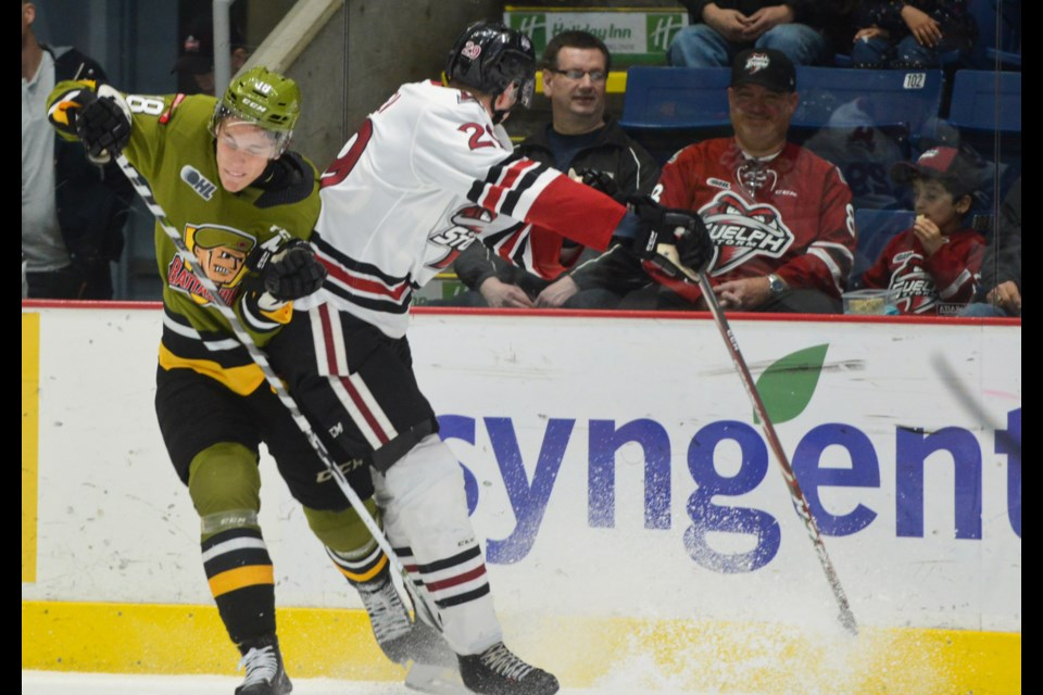 Fedor Gordeev finishes a hit on North Bay Battalion Matt Struthers Friday night at the Sleeman Centre. Tony Saxon/GuelphToday
