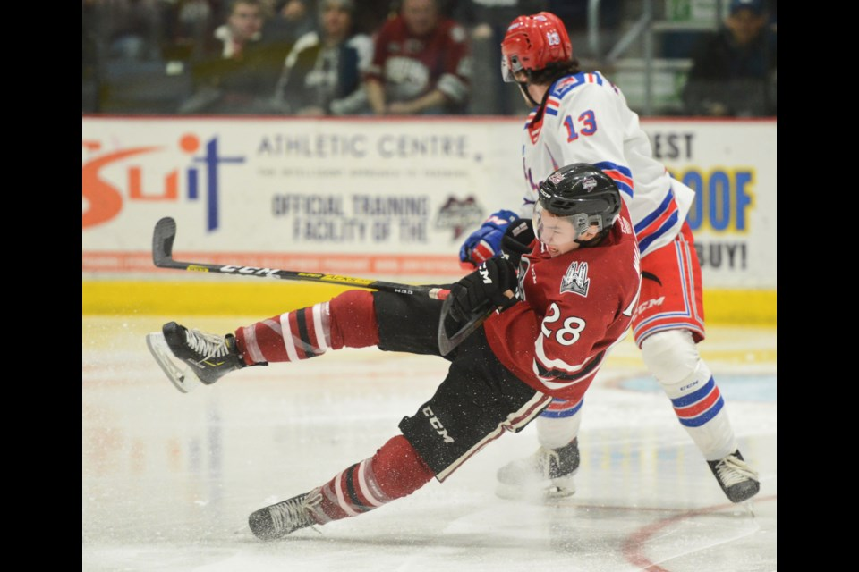 Cooper Walker of the Guelph Storm is hooked to the ice by Kithener's Riley Damiani Saturday night at the Sleeman Centre. Tony Saxon/GuelphToday
