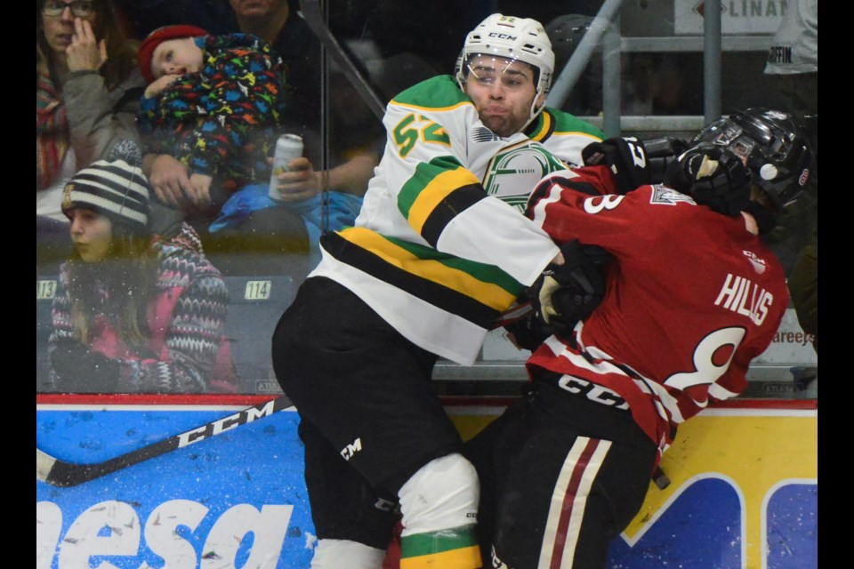 Markus Phillips of the London Knights hits the Guelph Storm's Cam Hillis along the boards Friday at the Sleeman Centre. Tony Saxon/GuelphToday