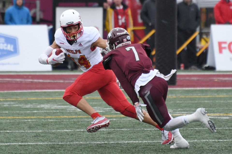 Kian Schaffer-Baker (14) of the Guelph Gryphons tries to get away from Mitch Garland (7) of the McMaster Marauders in Saturday's OUA football semifinal game at McMaster. Rob Massey for GuelphToday