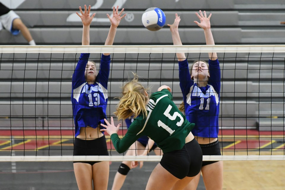 Alicia Breese (15) of the Guelph CVI Green Gaels tries to hit the ball between blockers Brooklyn Thomas (13) and Daniella Centurione of the Guelph CVI during Thursday night's District 10 high school junior girls' volleyball final at the Guelph Gryphons Athletic Centre. Rob Massey for GuelphToday