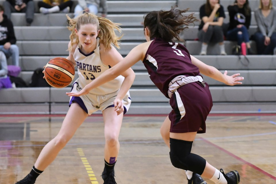 Sarah Cobey (13) of the Centennial Spartans tries to get away from the coverage of Elivia Garbuio (3) of the St. James Lions during Saturday night's District 10 high school senior girls' basketball final at the University of Guelph. Rob Massey for GuelphToday