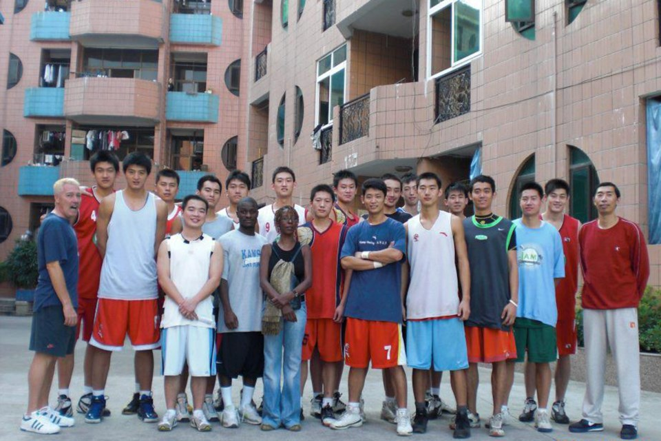 Former Guelph Gryphons men's basketball coach Tim Darling, far left, poses with one of the team's he's coached in Hong Kong. Submitted photo