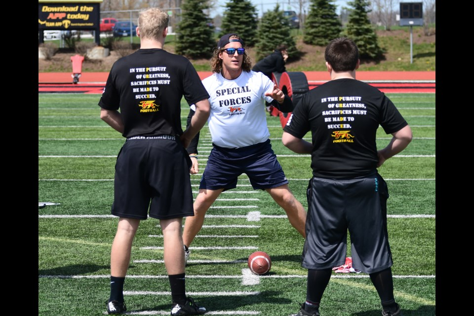 Jake Reinhart, centre, of the Toronto Argonauts gives pointers to a pair of participants in a Guelph Gryphons football camp at Alumni Stadium in 2016. Reinhart is back at Alumni Stadium for the Argos training camp. Rob Massey photo