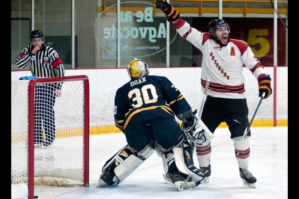 Kyle Neuber, right, of the Guelph Gryphons cheers after the Gryphons scored their first goal of the game on Windsor Lancers goaltender Michael Doan in OUA men's hockey playoff action Sunday night at the Gryphon Centre. Rob Massey for GuelphToday.