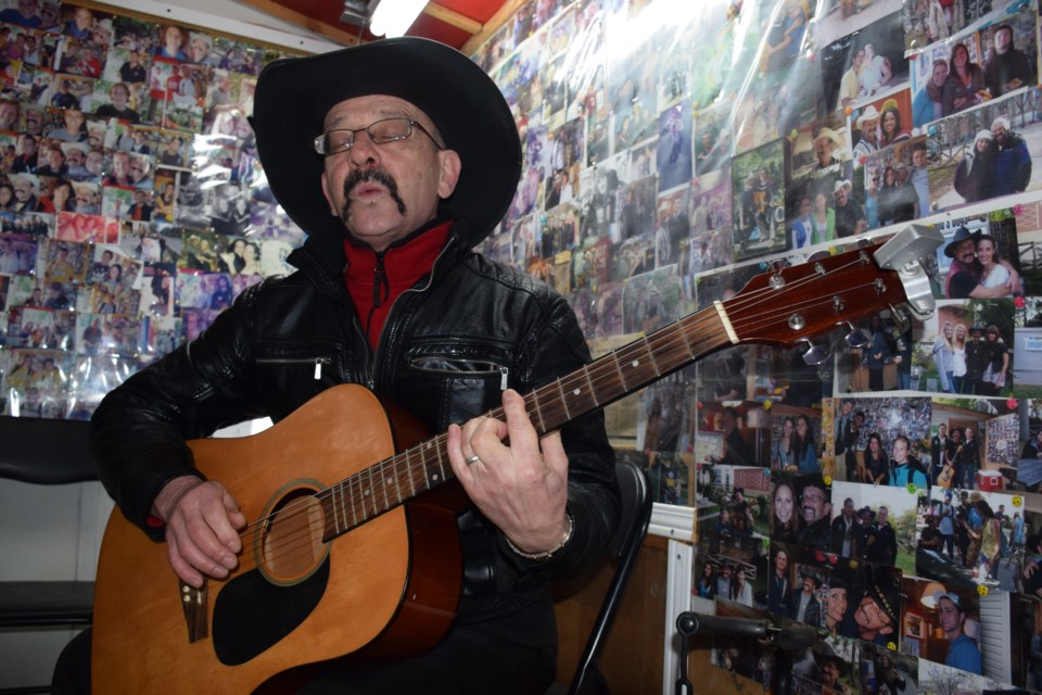 """Whistling a cowboy tune. The beloved  Bogdan """"Bob"""" Izdebski plays his old guitar and whistles a cowboy tune inside his Bob's Dogs on U of G campus. Students recently gave him a brand new guitar. Rob O'Flanagan/GuelphToday"""
